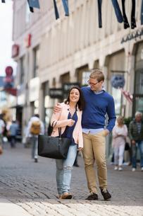 Sweden, Vastergotland, Gothenburg, Young couple walking and hugging in streetの写真素材 [FYI02205407]