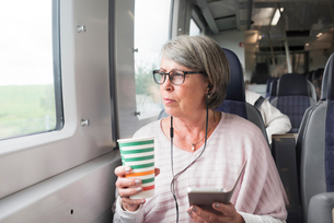 Sweden, Senior woman holding paper cup and phone on trainの写真素材 [FYI02205433]