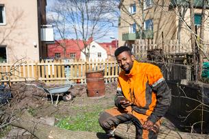 Sweden, Sodermanland, Portrait of arborist sitting on logの写真素材 [FYI02205454]