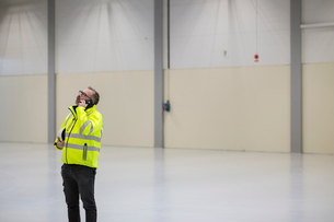 Sweden, Mature man wearing protective workwear talking on telephone in industrial hallの写真素材 [FYI02205507]