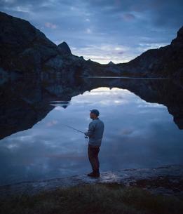 Norway, Lofoten, Fjerddalsvatnet, Man fishing in lake at dawnの写真素材 [FYI02205508]