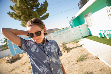 USA, California, Boy (14-15) wearing sunglasses standing outside of houseの写真素材 [FYI02205512]