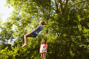Sweden, Oland, Two girls (8-9, 10-11) playing on sunny dayの写真素材 [FYI02205566]
