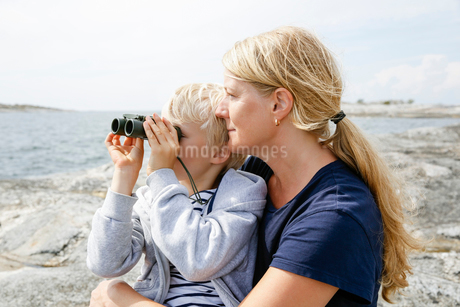 Sweden, Stockholm Archipelago, Sodermanland, Orno, Mother and son (6-7) sitting on rocky seashore, sの写真素材 [FYI02205571]