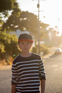 USA, California, Pacific Grove, Portrait of boy (14-15) standing in street at sunsetの写真素材 [FYI02205575]
