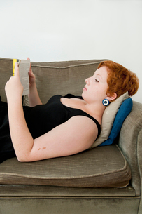 Young redhair woman lying on sofa and readingの写真素材 [FYI02205593]