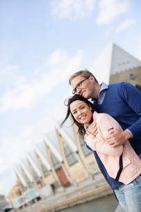 Sweden, Vastergotland, Smiling young couple against buildingsの写真素材 [FYI02205671]