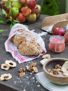 Sweden, Bread, nuts, apple puree and fresh apples on wooden tableの写真素材 [FYI02205679]