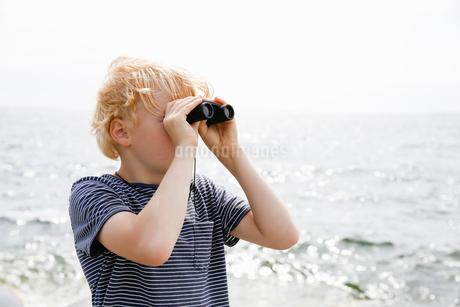 Sweden, Stockholm Archipelago, Sodermanland, Orno, Boy (8-9) looking through binocularsの写真素材 [FYI02205686]