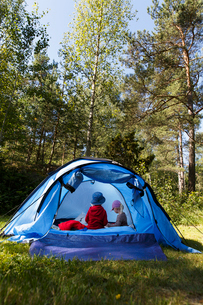 Sweden, Sodermanland, Trosa, Kids (2-3, 4-5) sitting in blue tentの写真素材 [FYI02205708]