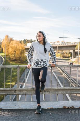 Sweden, Vastergotland, Gothenburg, Young woman leaning against railing on footbridgeの写真素材 [FYI02205732]