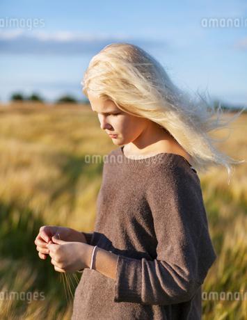 Denmark, Mon, Teenage girl (16-17) playing with grassの写真素材 [FYI02205736]