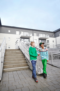 Sweden, Vastra Gotaland, Grimmered, Boys (8-9) standing by stairs and talkingの写真素材 [FYI02205740]