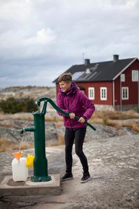Sweden, Stockholm Archipelago, Sodermanland, Huvudskar, Mature woman pumping water form wellの写真素材 [FYI02205746]