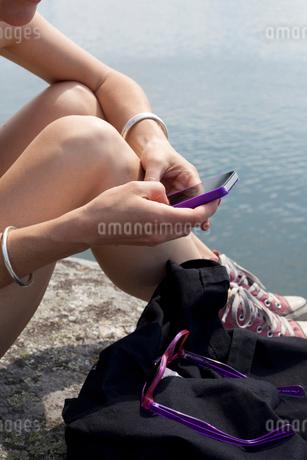 Sweden, Stockholm Archipelago, Mature woman on riverbank textingの写真素材 [FYI02205764]