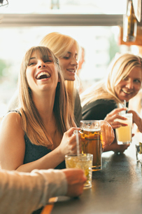 Sweden, Women laughing and drinking beer in barの写真素材 [FYI02205802]