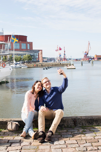 Sweden, Vastergotland, Gothenburg, Young couple sitting on promenade and taking selfie with smart phの写真素材 [FYI02205811]