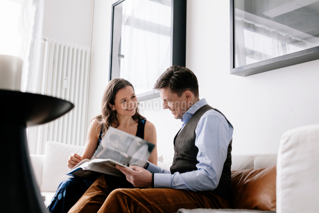 Germany, Couple sitting on sofa and reading bookの写真素材 [FYI02205821]