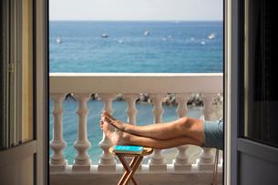 Italy, Cinque Terra, Monterosso, Man resting on balcony with sea viewの写真素材 [FYI02205832]