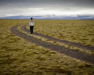Iceland, Sudurland, Hiker on dirt road through wilderness towards mountain range on horizonの写真素材 [FYI02205848]