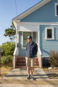 USA, California, Pacific Grove, Mature man standing in front of blue houseの写真素材 [FYI02205855]