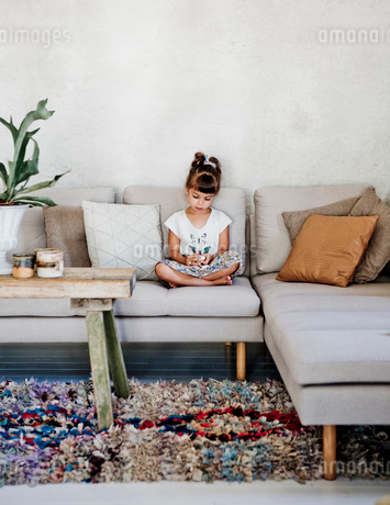 Sweden, Girl (4-5) sitting on sofaの写真素材 [FYI02205856]