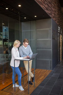 Finland, Colleagues using laptop in lobbyの写真素材 [FYI02205876]