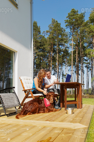 Sweden, Sodermanland, Ronninge, Couple with dog sitting on patioの写真素材 [FYI02205886]