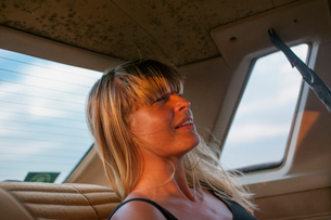 Sweden, Blonde woman on back seat of carの写真素材 [FYI02205887]