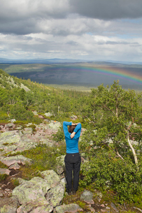 Sweden, Dalarna, Fulufjallet, Man standing on hill and looking at landscape with rainbowの写真素材 [FYI02205895]