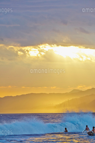 USA, California, Los Angeles, Santa Monica Beach, Young men in ocean at sunsetの写真素材 [FYI02205912]