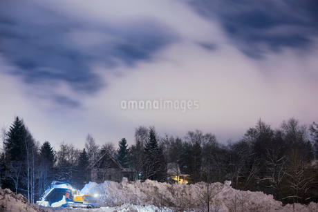 Finland, Pirkanmaa, Tampere, Excavator removing snow next to houses in forestの写真素材 [FYI02205919]