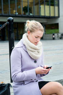 Sweden, Vastra Gotaland, Gothenburg, Young woman sittings on steps and using smart phoneの写真素材 [FYI02205920]