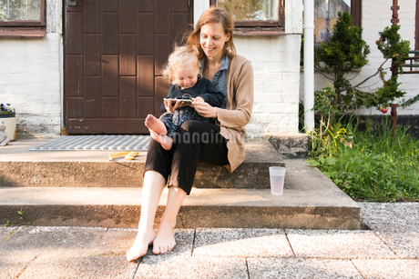 Sweden, Skane, Mother and son (2-3) sitting on steps and using tabletの写真素材 [FYI02205930]