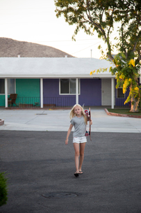 USA, California, Girl (12-13) carrying skateboard with motel in backgroundの写真素材 [FYI02205964]