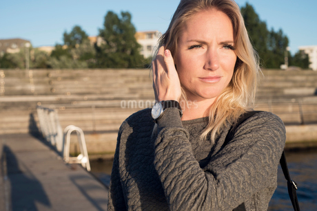 Sweden, Skane, Malmo, Portrait of young blonde woman on pierの写真素材 [FYI02205967]