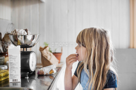 Sweden, Little girl (4-5) cookingの写真素材 [FYI02205983]