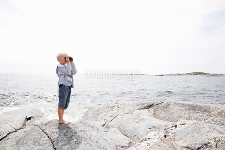 Sweden, Stockholm Archipelago, Sodermanland, Orno, Boy (6-7) standing on rocky seashore and lookingの写真素材 [FYI02205994]