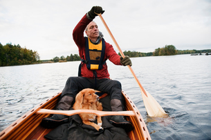 Sweden, Smaland, Mature man and dog in boat on lakeの写真素材 [FYI02206025]