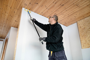 Sweden, Mature man painting wallの写真素材 [FYI02206053]