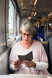 Sweden, Senior woman sitting on train and using phoneの写真素材 [FYI02206063]