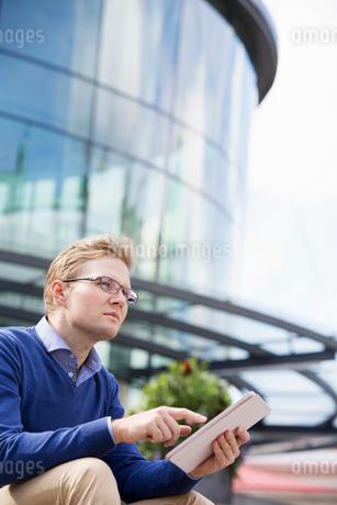 Sweden, Vastergotland, Gothenburg, Young man sitting against glass building and using digital tabletの写真素材 [FYI02206076]