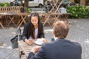 Sweden, Skane, Malmo, Man and woman drinking coffee and using smartphones in sidewalk cafeの写真素材 [FYI02206081]