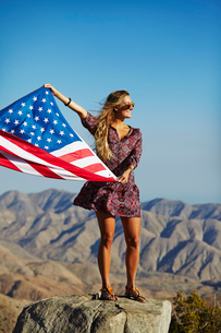 USA, California, Young blonde woman holding US flag in front of mountain landscapeの写真素材 [FYI02206086]