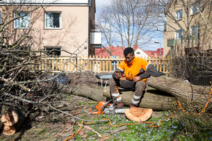 Sweden, Sodermanland, Arborist sitting on logの写真素材 [FYI02206101]