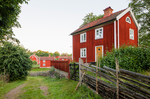 Sweden, Smaland, Stensjo, Traditional wooden fence and brown houseの写真素材 [FYI02206106]
