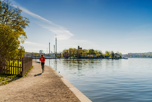 Sweden, Stockholm, Skeppsholmen, Man running near harborの写真素材 [FYI02206119]