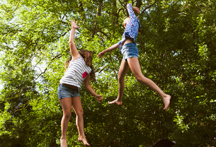Sweden, Oland, Two girls (8-9, 10-11) jumpingの写真素材 [FYI02206132]