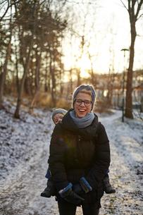 Sweden, Sodermanland, Stockholm, Johanneshov, Hammarbyhojden, Laughing mid adult woman carrying sonの写真素材 [FYI02206139]