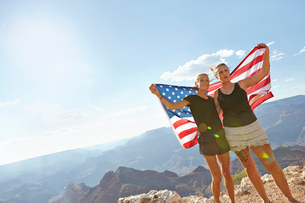 USA, Arizona, Young women embracing and holding US flag against Grand Canyonの写真素材 [FYI02206140]